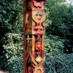 Eine 2,5 Meter hohe Holzskulptur mit farbenfrohen Verzierungen die Vögel oder Symbole darstellen. Hergestellt von Max Holst: Malerei für Öl-und Acryl-Bilder, Gemälde und Porträts, Grafikdesign und handgefertigte Objekte aus der Lüneburger Heide.